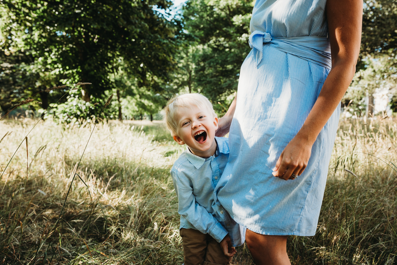 Boy laughs whilst playing with his pregnant mother by Hampshire Maternity Photographer Evie Winter