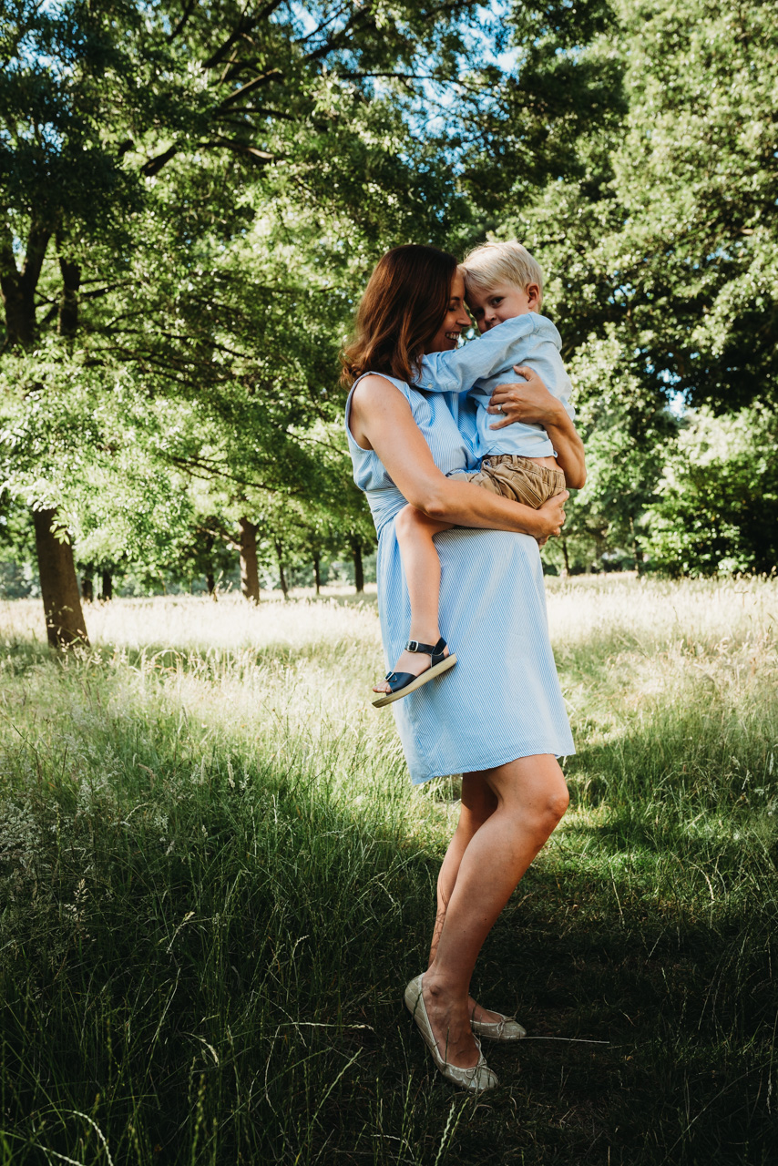 Pregnant mother hugs young boy by Hampshire Maternity Photographer Evie Winter