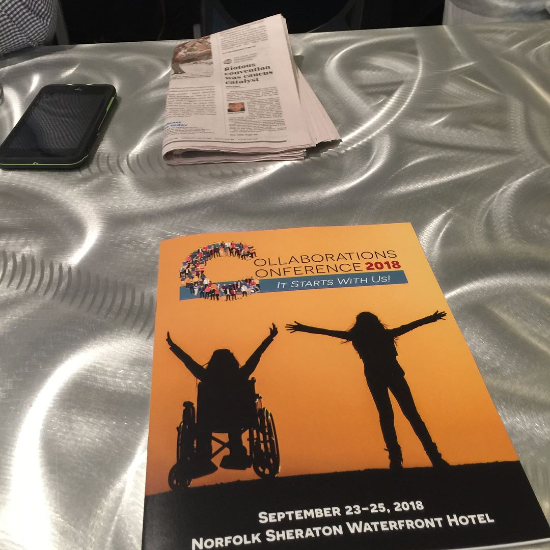 PHOTO: Program from attending.The 2018 Collaborations Conference. The program depicts two silhouettes of people. One person with a disability in a wheelchair and one able-bodied person holding their arms up in victory.