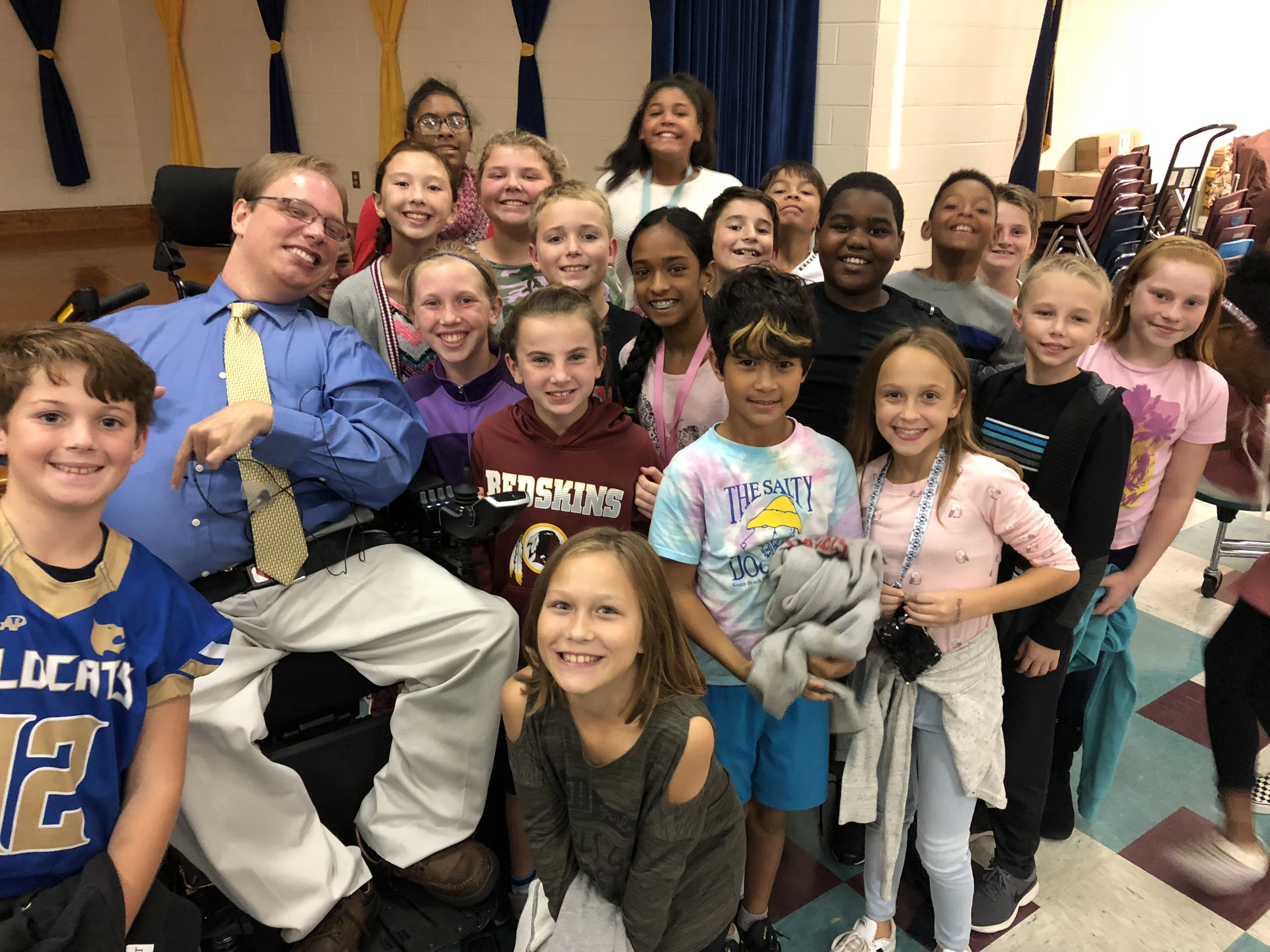 PHOTO: Matthew taking a group photo with several smiling fourth and fifth graders from Woolridge Elementary School after his Positively Inclusive presentation.