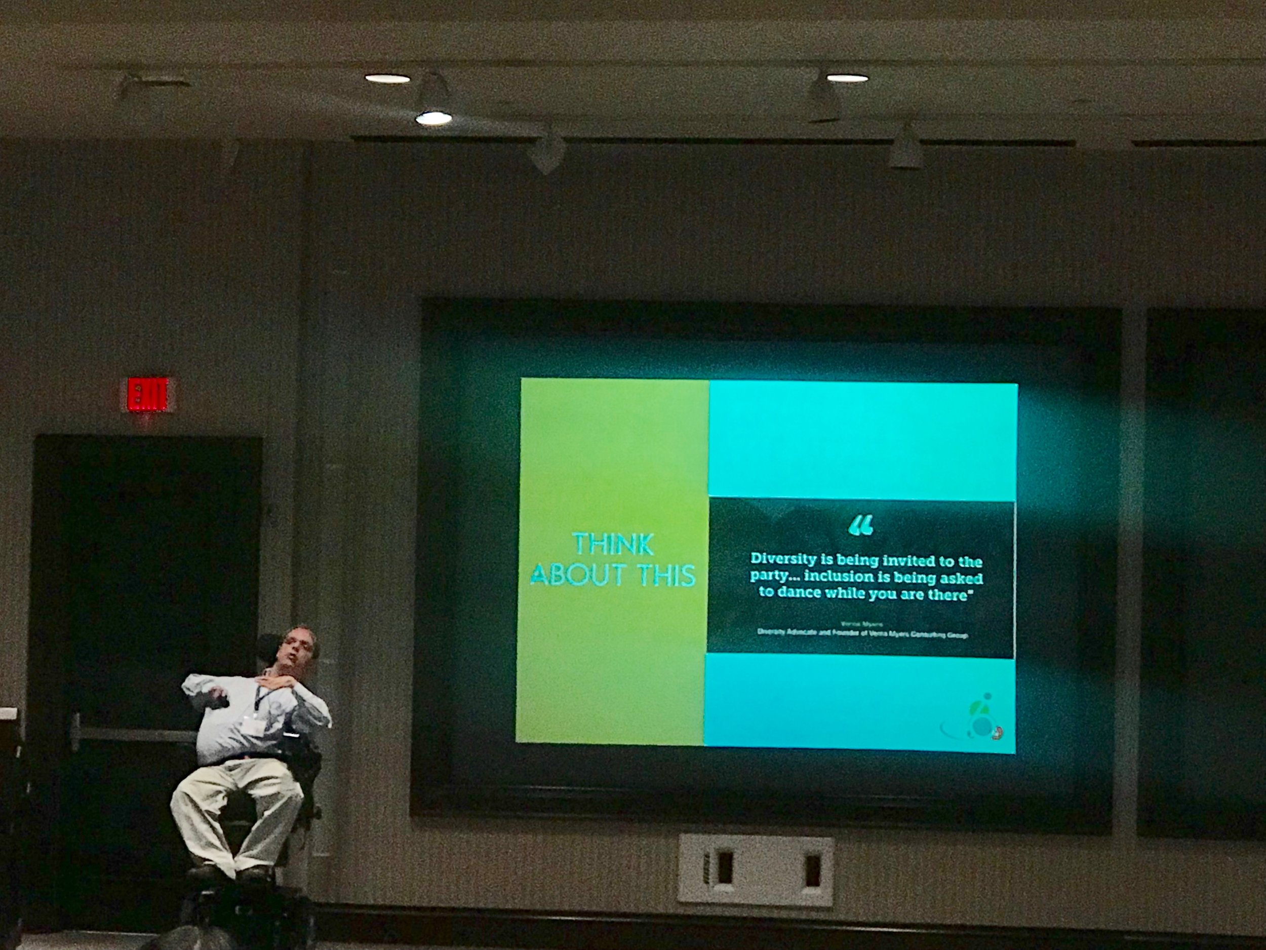 PHOTO: Matthew, on stage next to a screen, serving as the keynote speaker at the Regional Assistive Technology Symposium in Roanoke, Virginia. The keynote was about how Matthew has utilized assistive technology throughout his life.