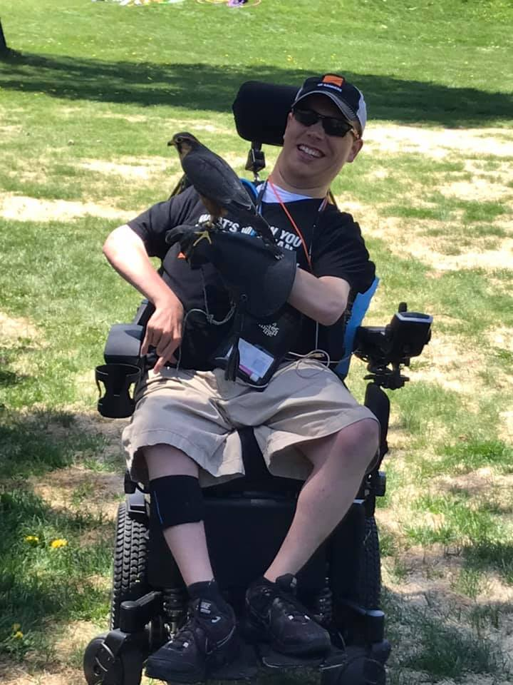 PHOTO: Matthew, in his wheelchair, in a black shirt and cap with khaki shorts holding a falcon with a smile on his face. This took place at The No Barriers Summit.