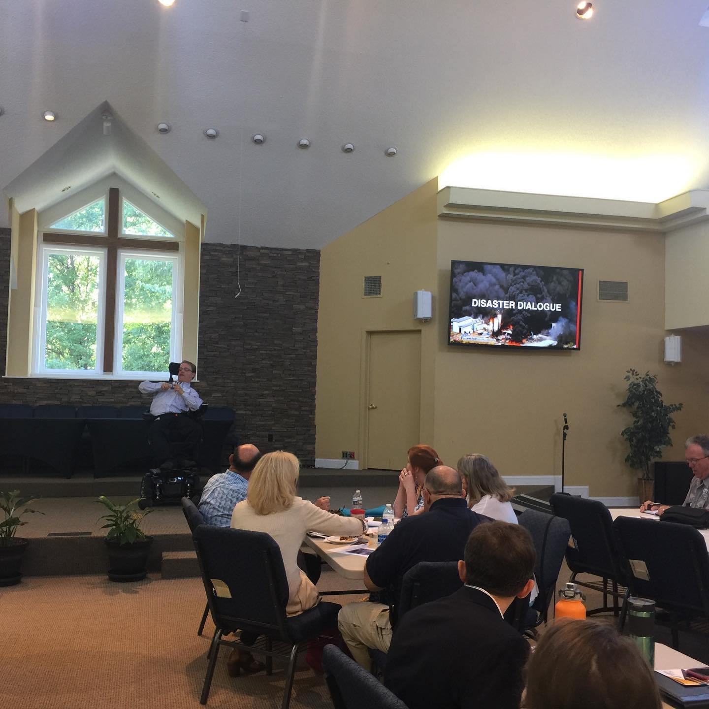 PHOTO: Matthew on stage, in a blue shirt, in his wheelchair. He front of an audience listening to his keynote. A TV to the right of him reads Disaster Dialog. There is also a picture of a fire on the screen. This keynote took place as part of The Virginia Mass Care Symposium.