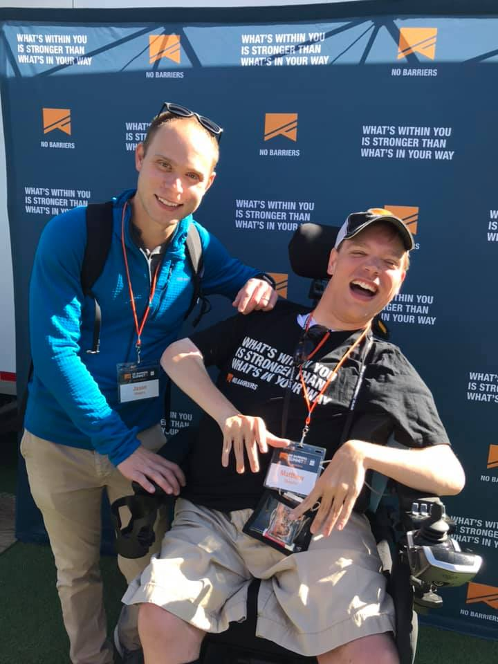 PHOTO: Matthew, in his wheelchair in a black shirt black hat and khaki shorts smiling. Standing next to him is his brother, Jason. He is smiling in a blue shirt and khaki pants They are having their picture taken in front of a blue backdrop that reads No Barriers.