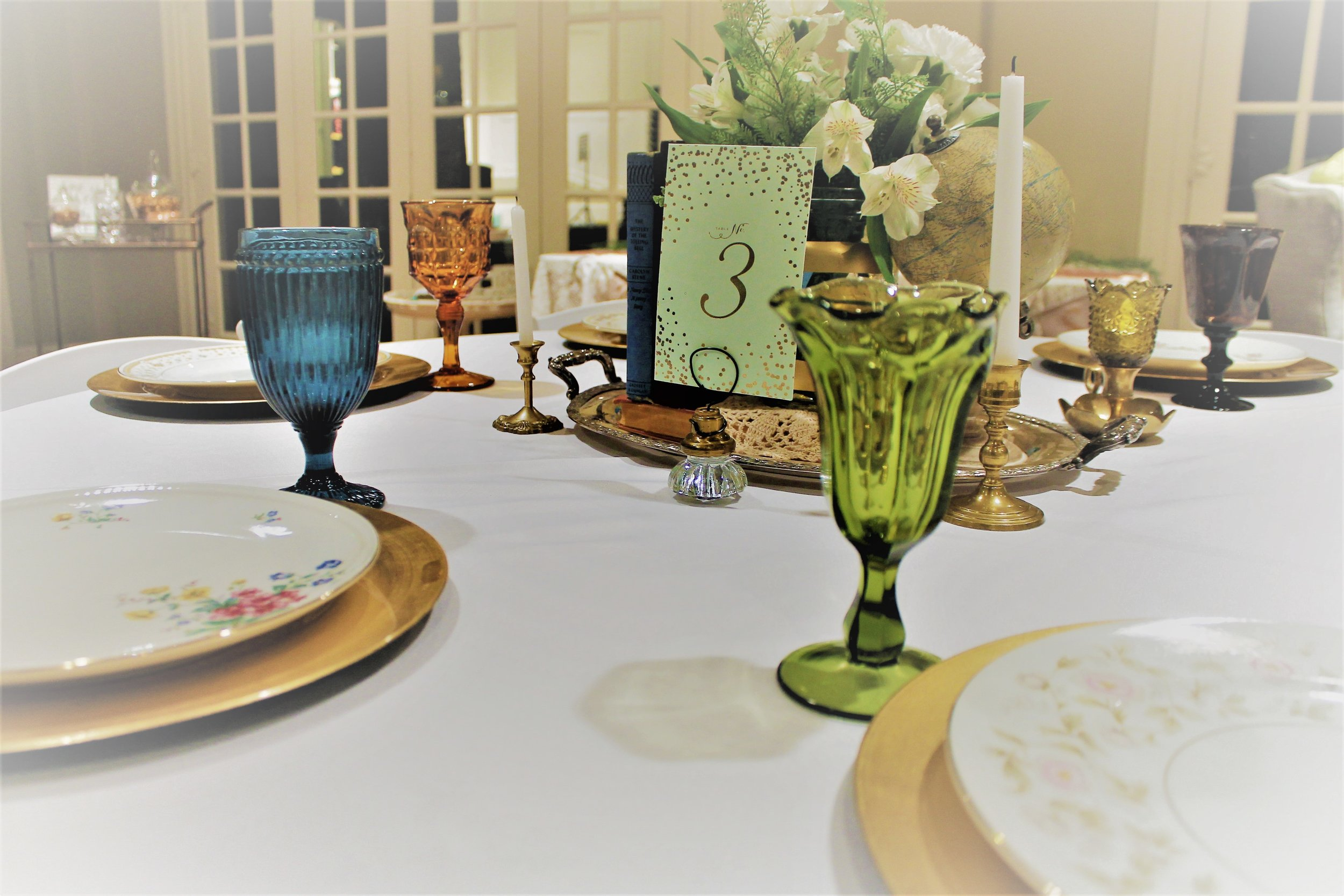 Vintage colored goblets, books, and globes