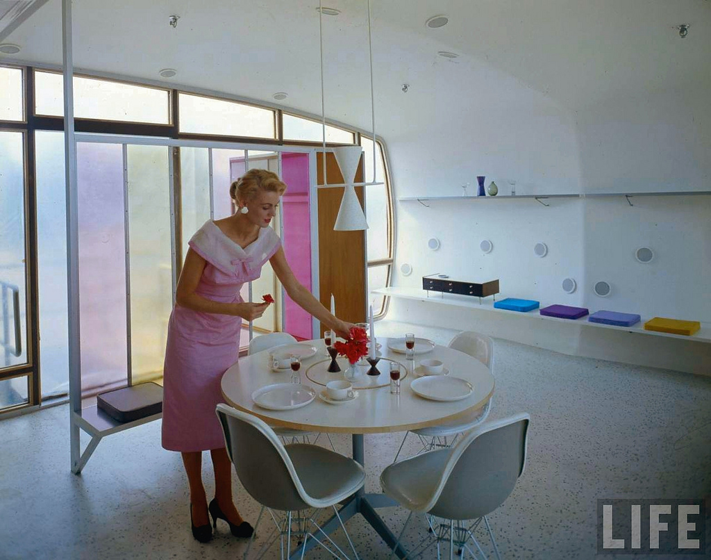 The Woman of the Future sets the table with a bouquet of plastic flowers.