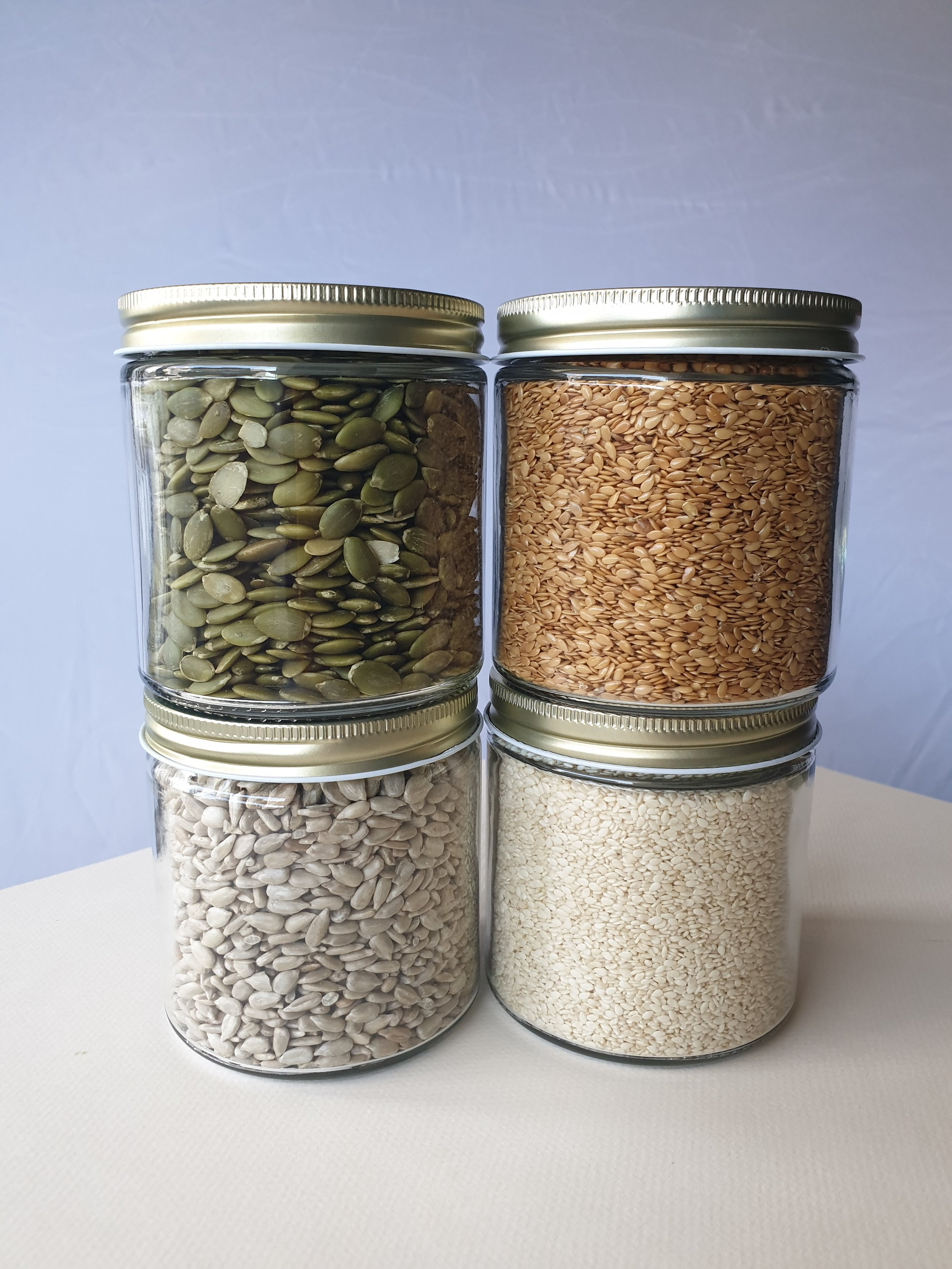 Clockwise direction: Raw pumpkin seeds, raw flaxseeds, raw white sesame seeds and raw hulled sunflower seeds