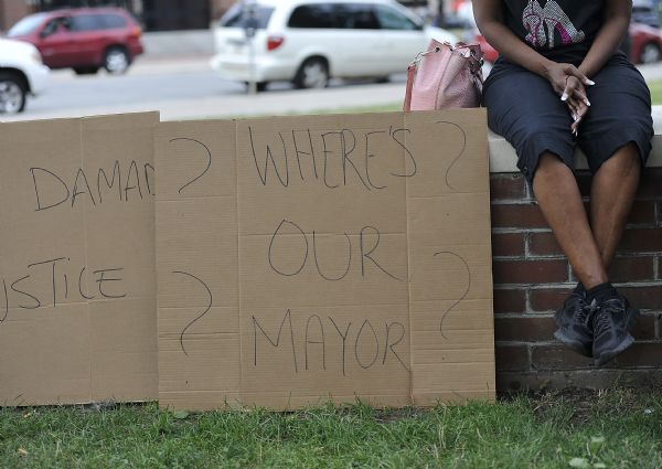 """Erie, PA (July 28, 2016) Woman sitting with signs stating """"We Demand Justice"""" and """"Where's Our Mayor"""" during a peace rally conducted by members of the Citizens and Clergy, Take Back Our Streets Movement, and citizens in Downtown Erie. (Photo Credit: Lauren Benzo )"""
