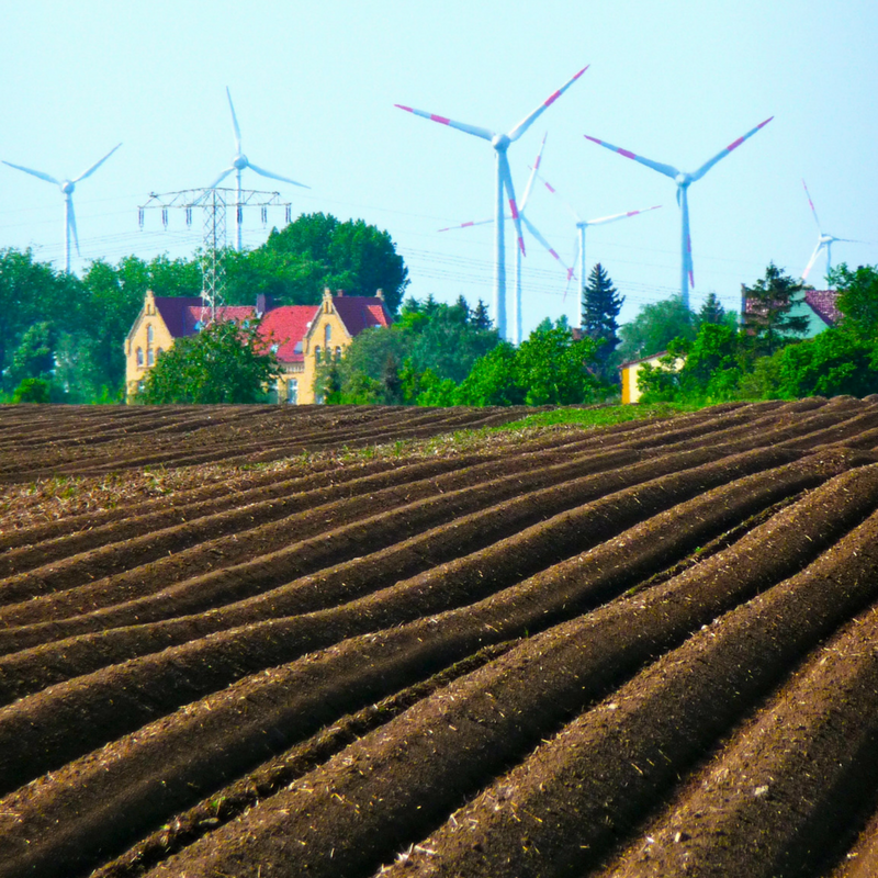 plowed farm field with home and wind turbines in background