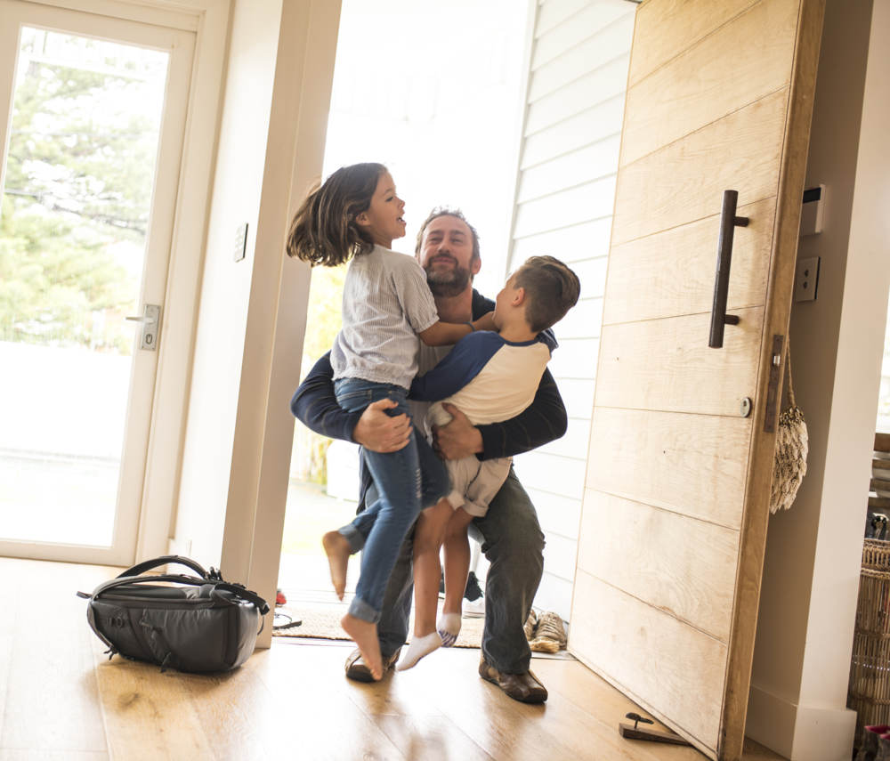 dad and two kids hugging in house
