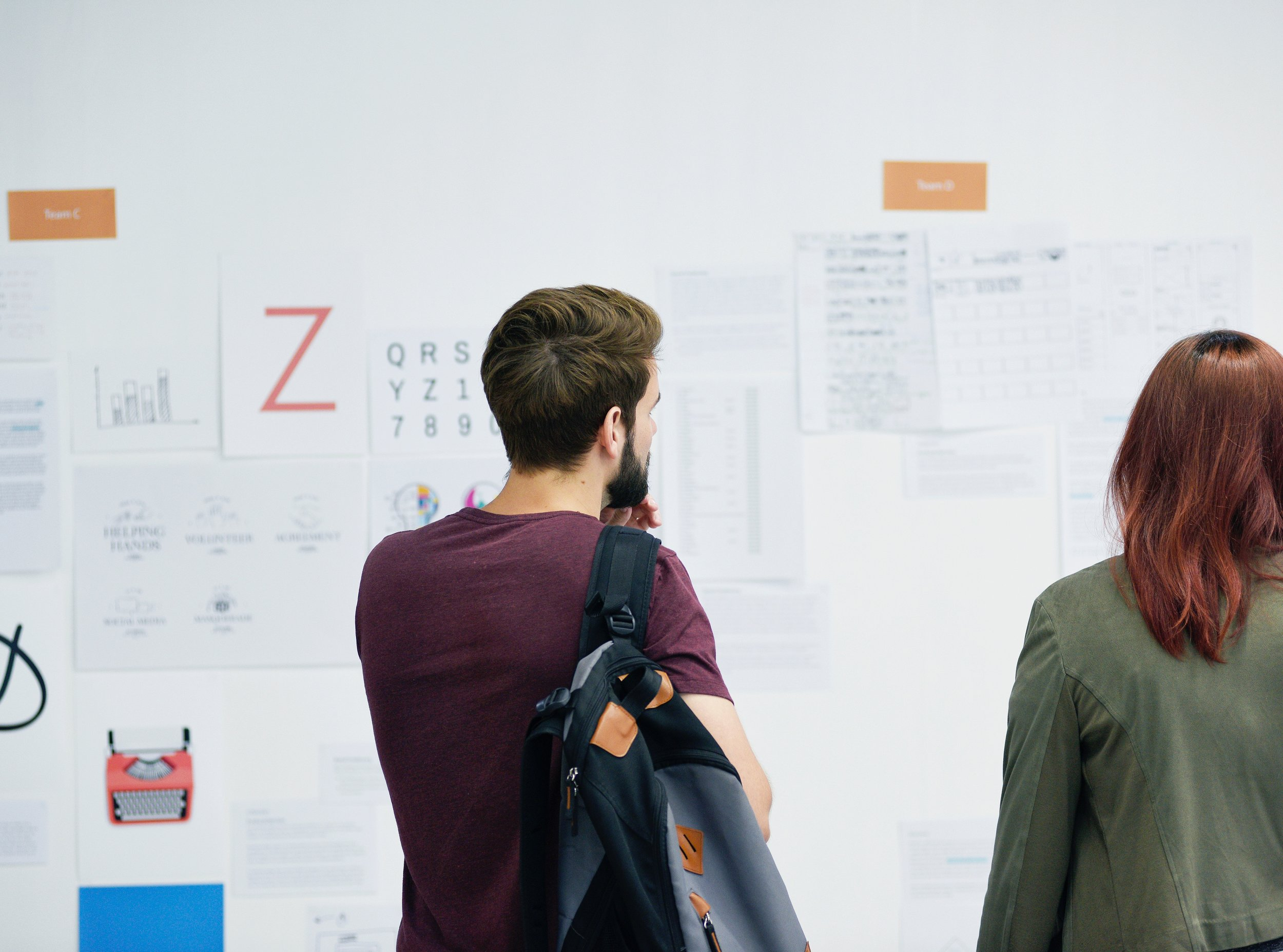 man and woman looking at notice board