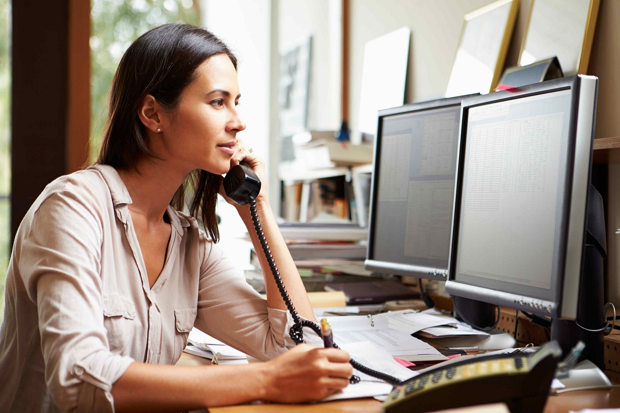 working woman on the phone while looking at desktop