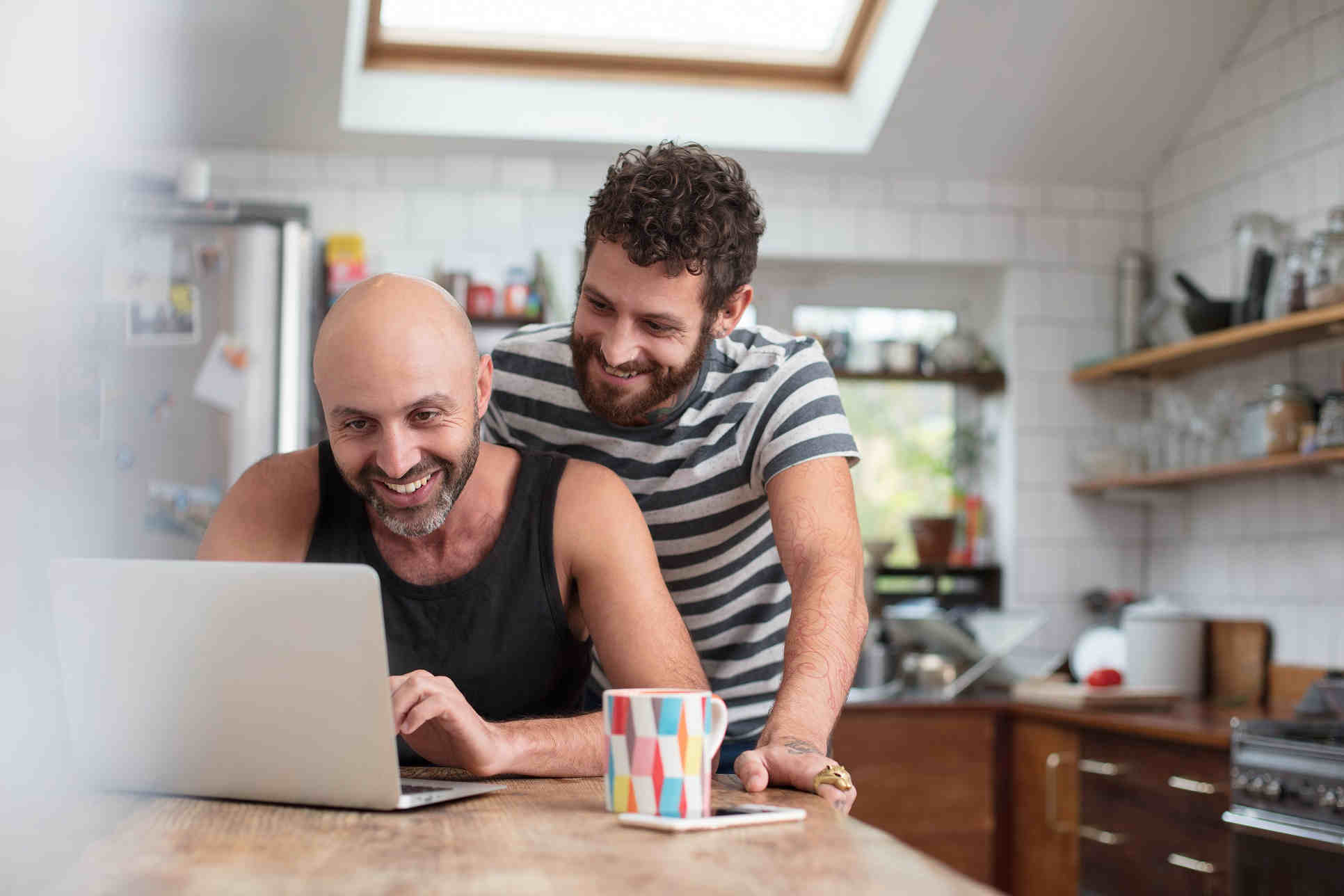 two men looking and smiling at laptop in kitchen
