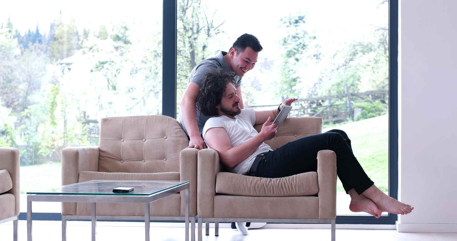 two men reading book on armchair
