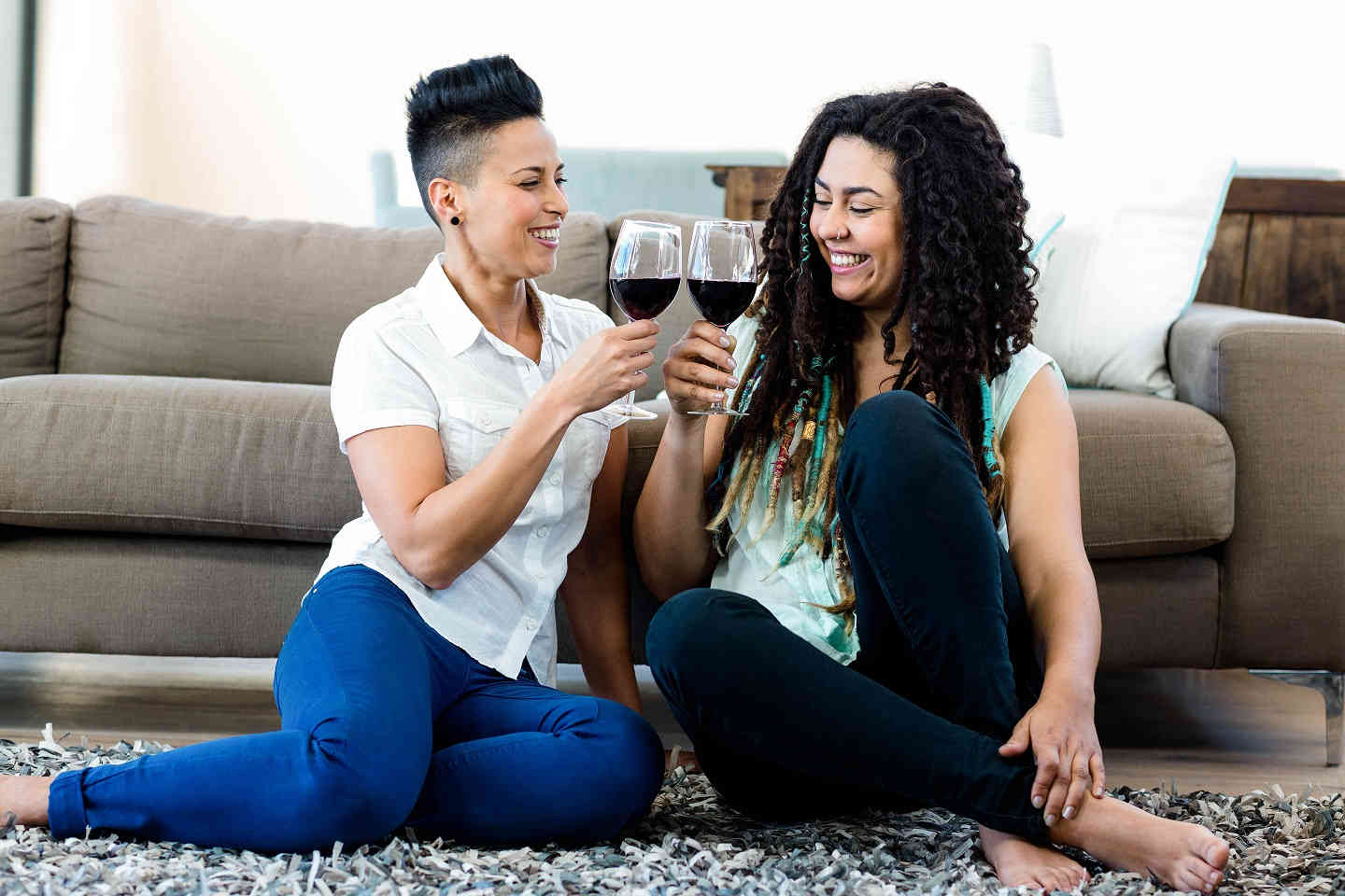 smiling-lesbian-couple-drinking-wine-new-home