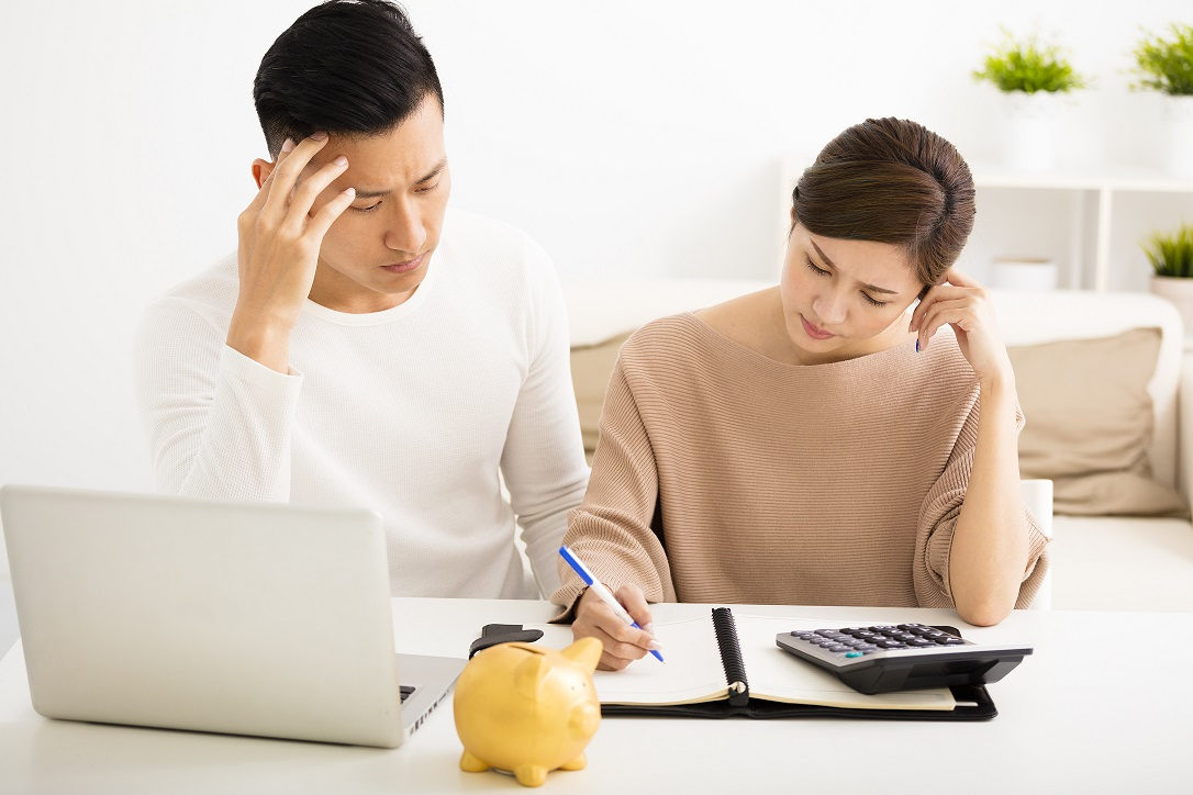 young couple writing notes with calculator and laptop