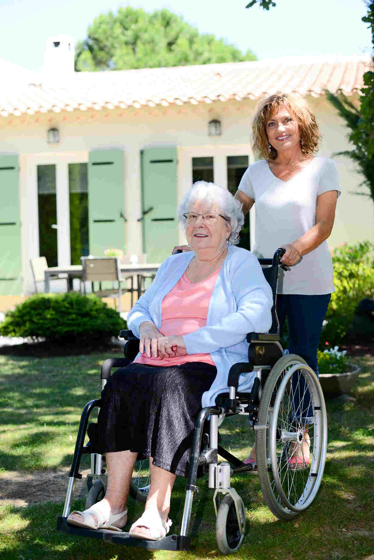 young woman posing with elderly woman in wheelchair in front of home