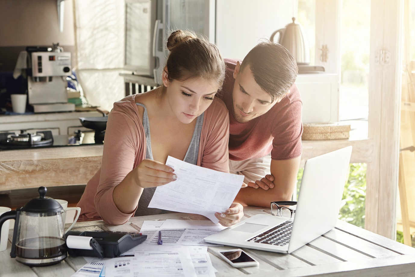 young couple looking over document in kitchen with laptop