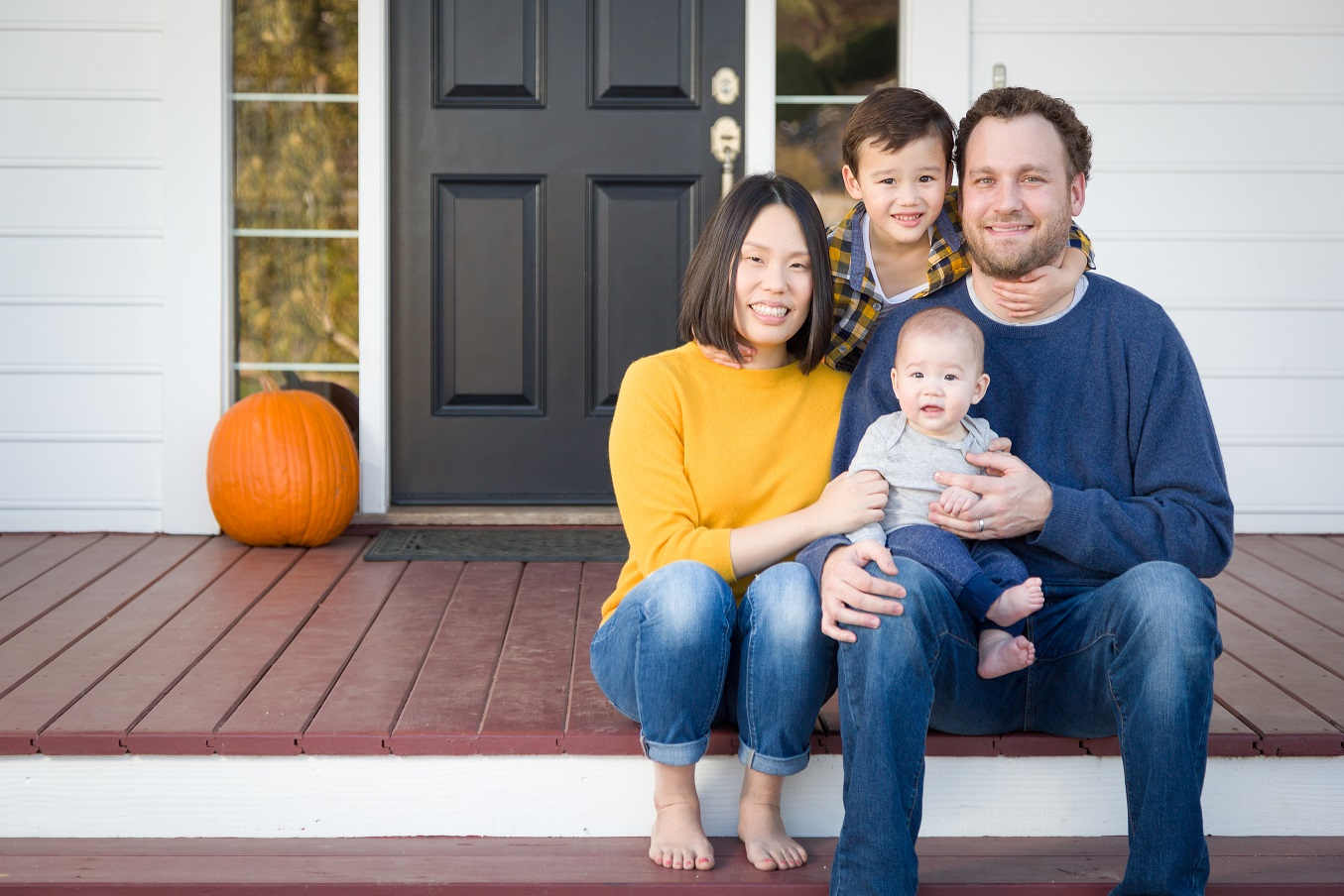 young family seated on front stoop
