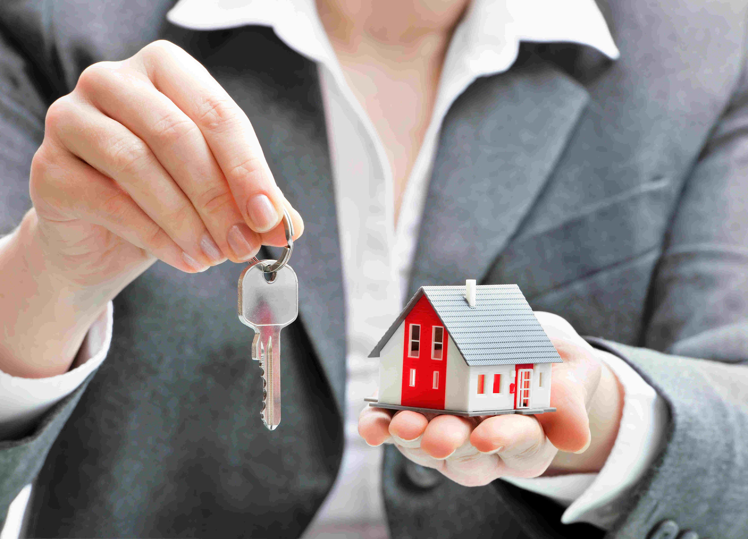 man holding toy house in one hand and handing over keys in other hand