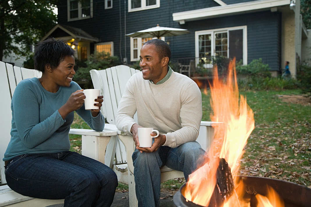 frican American couple having coffee by fire outside home