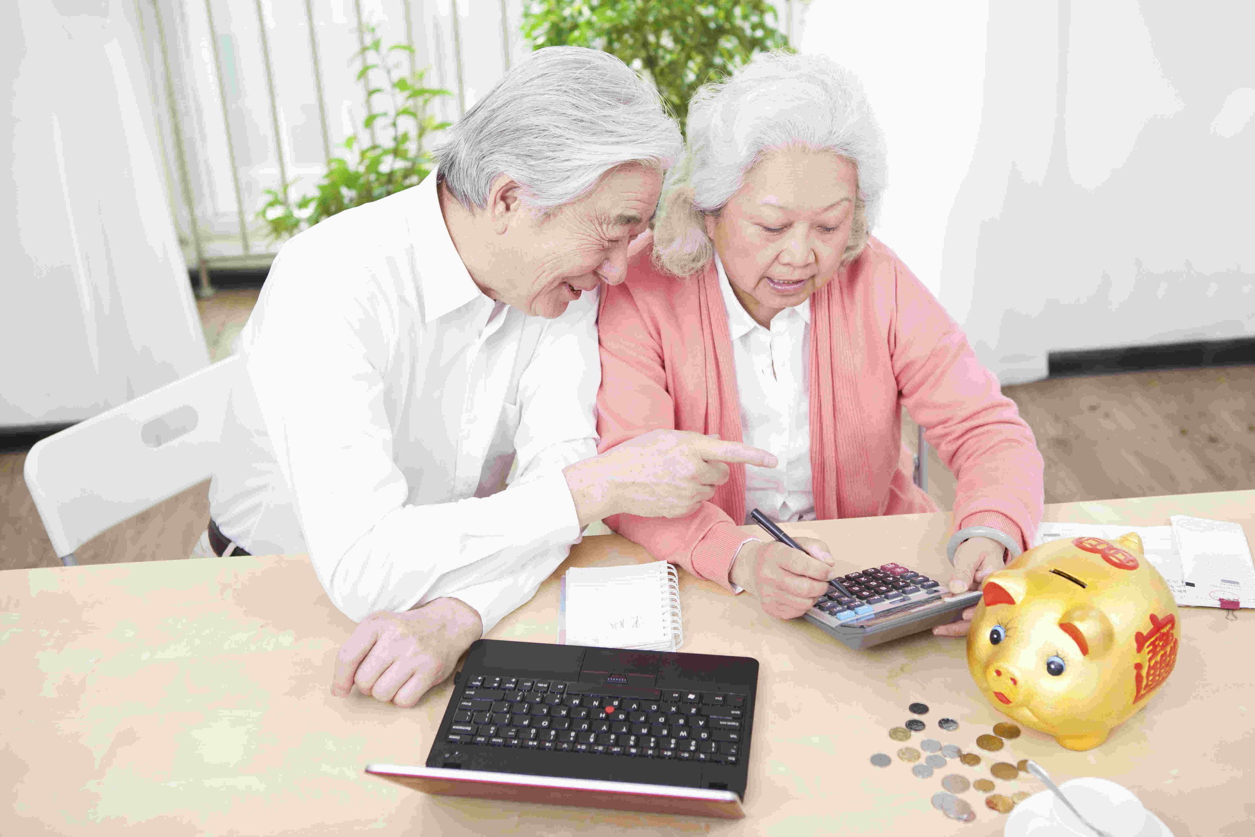 elderly Asian couple using calculator with piggy bank and laptop