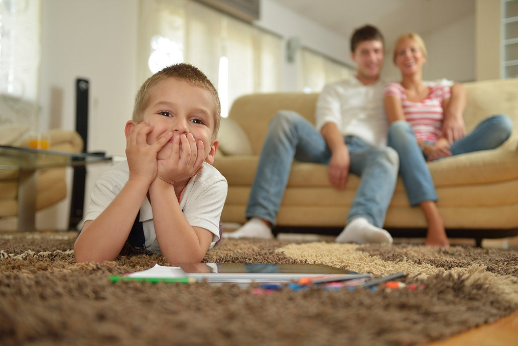 boy lying on the floor on stomach smiling with parents in the background