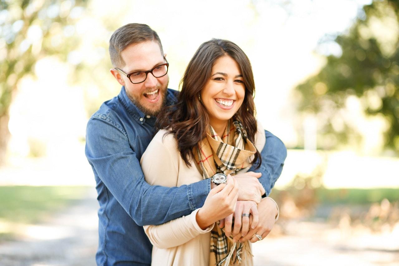 smiling man hugging smiling woman from behind