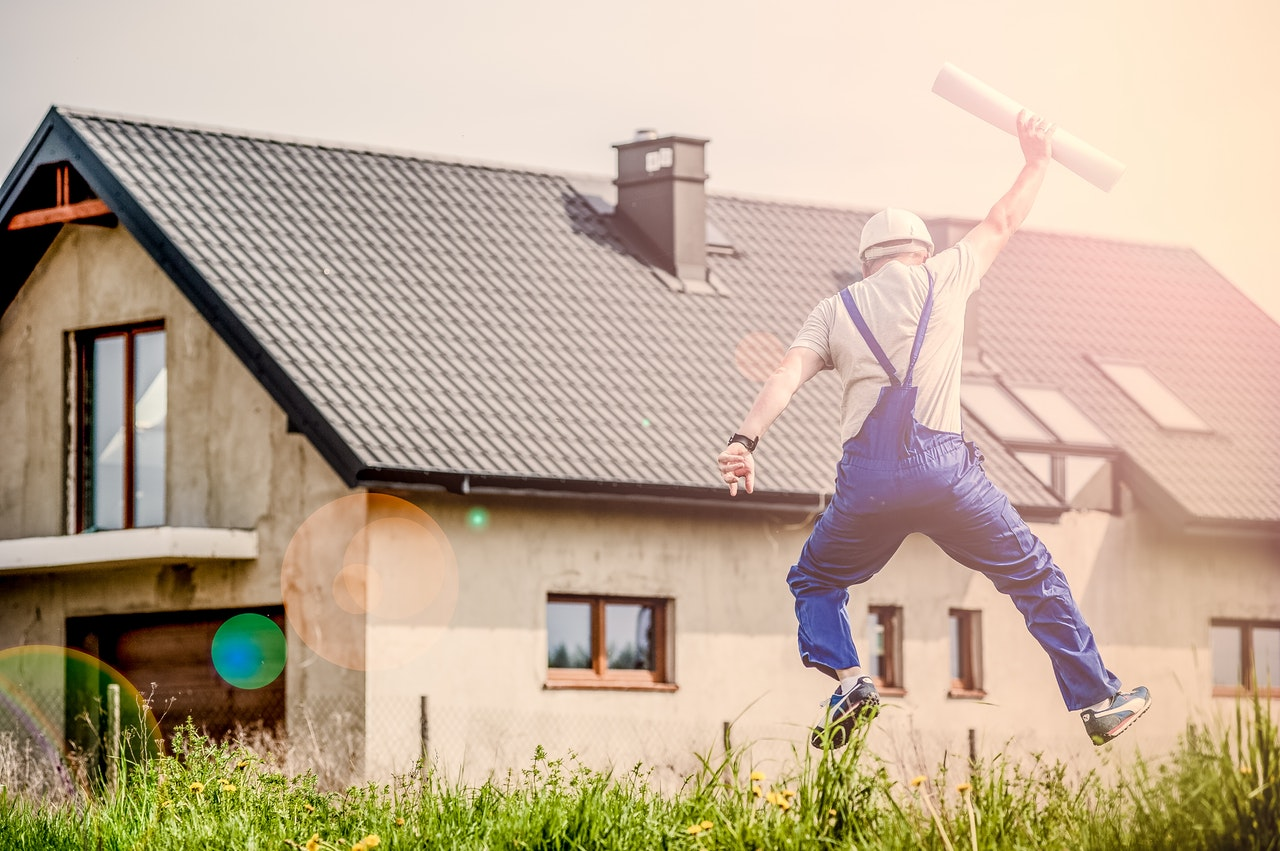 man in overalls jumping into the air holding house plans in front of house
