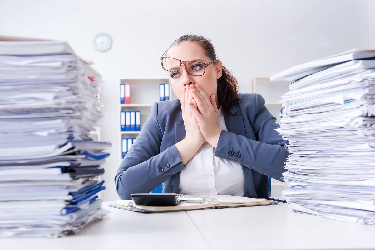 woman with distraught look staring at huge stack of documents