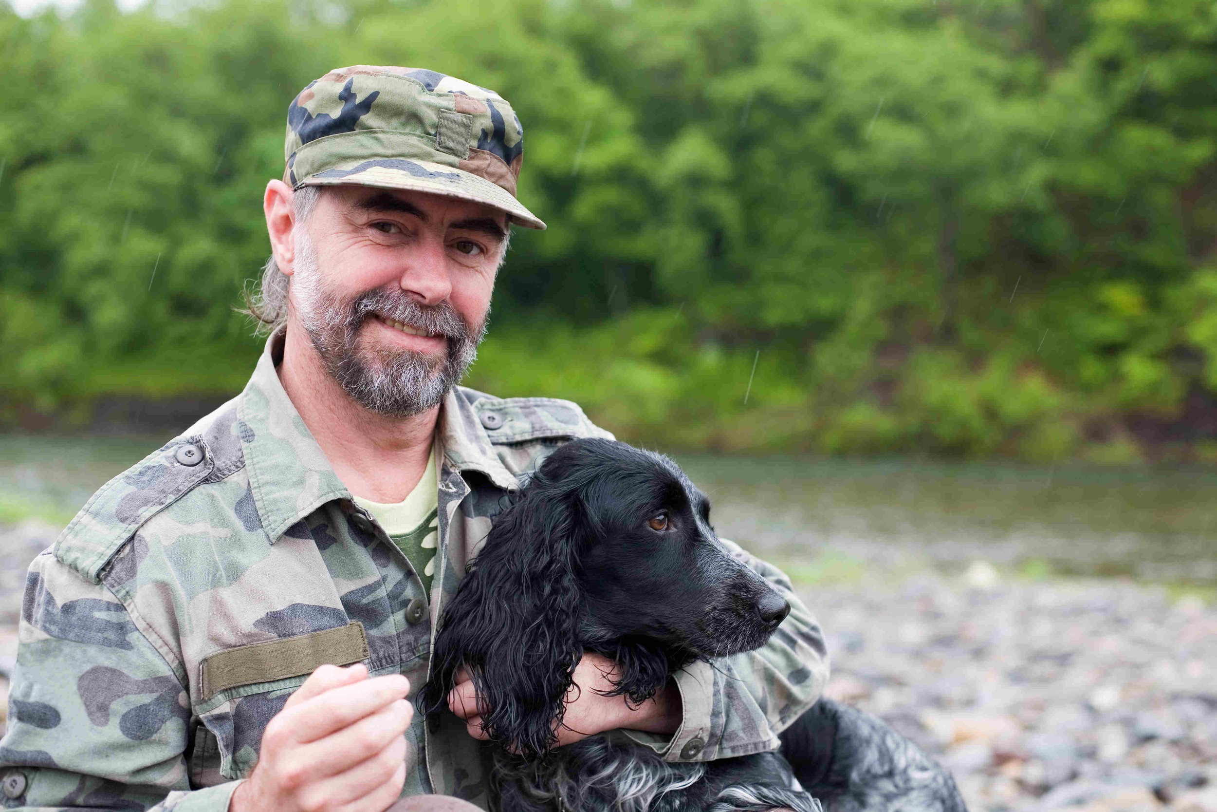 old male veteran soldier holding black dog
