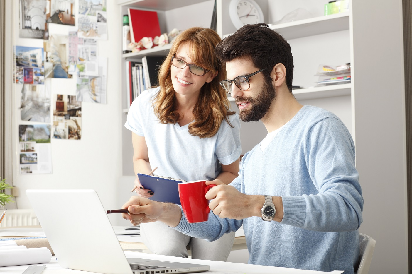 man drinking coffee and pointing to laptop with female colleague