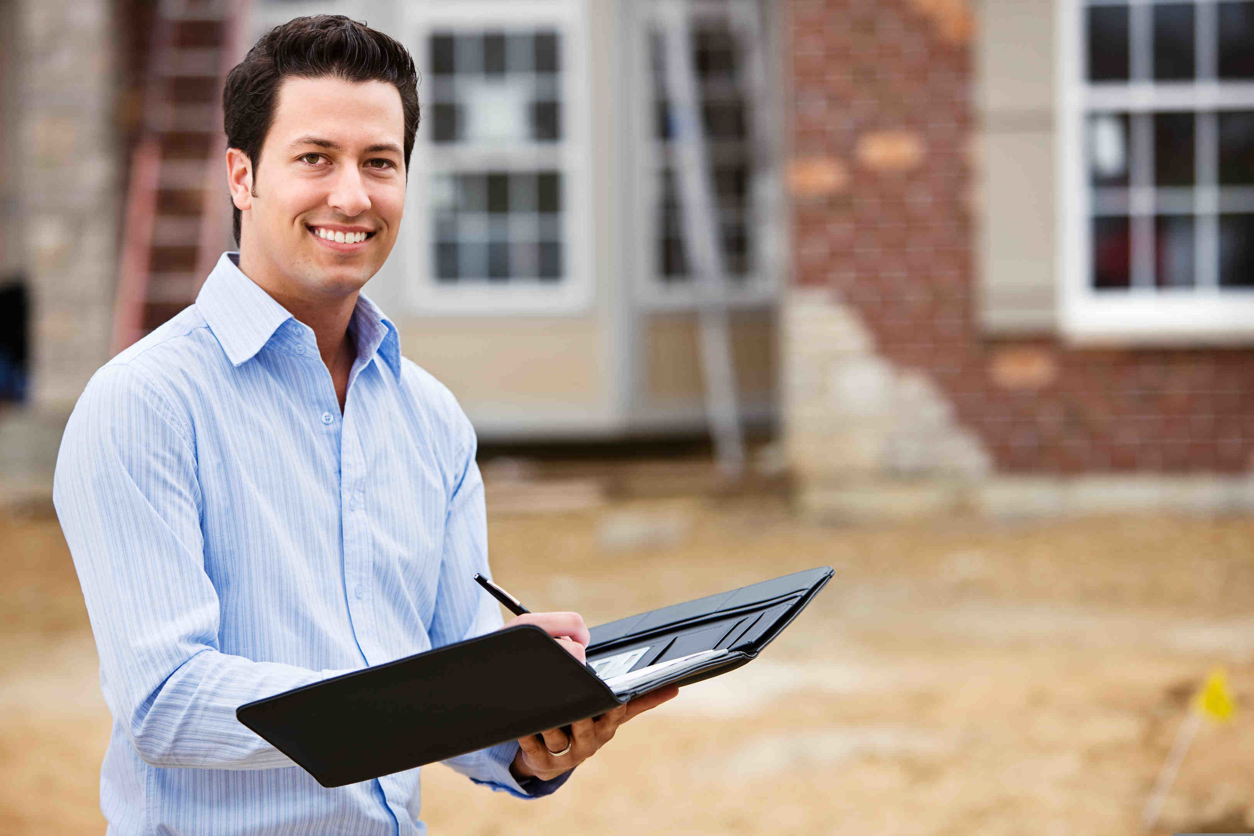 real estate agent smiling and writing notes in front of house