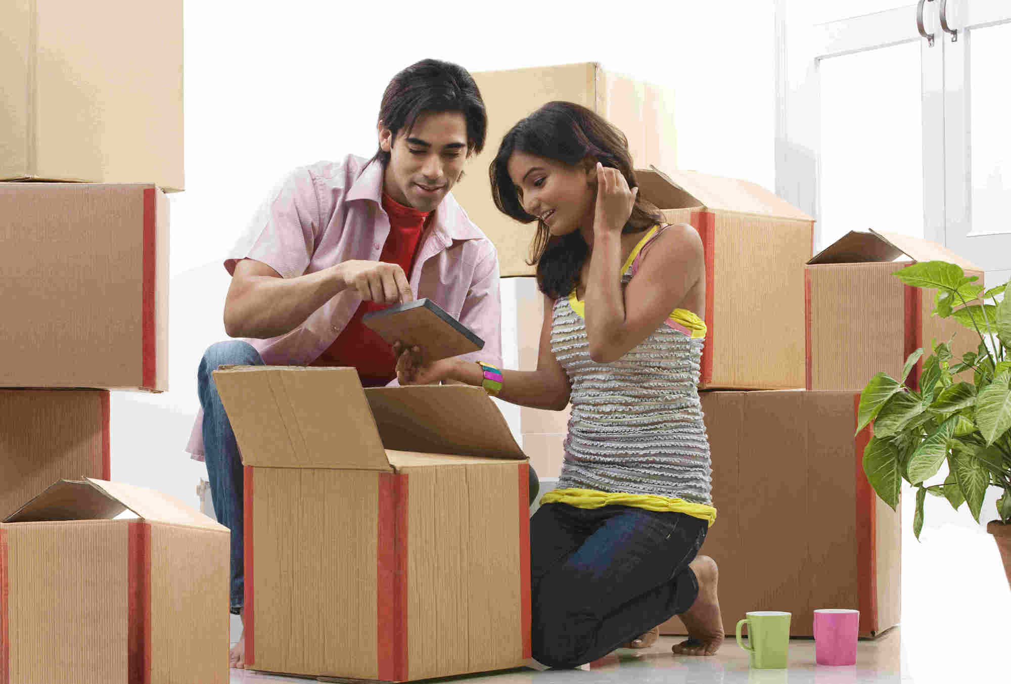 young couple viewing photos from moving boxes