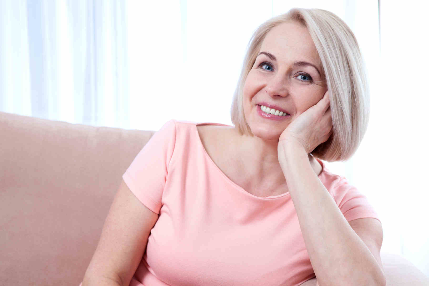 woman seated on sofa smiling