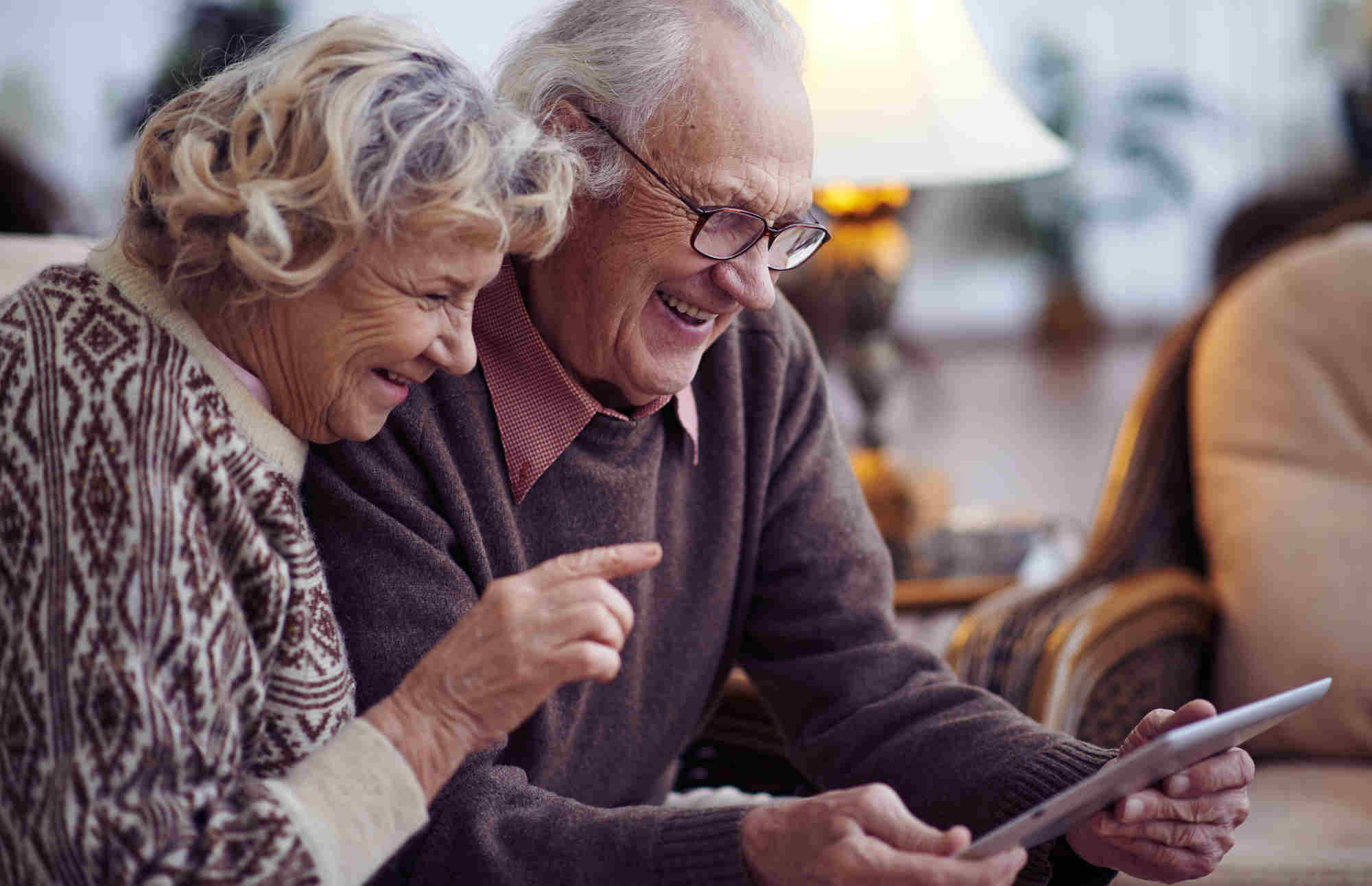 grandparents smiling at tablet