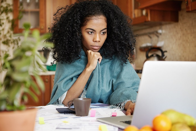 young african american woman looking attentively at laptop screen in the kitchen