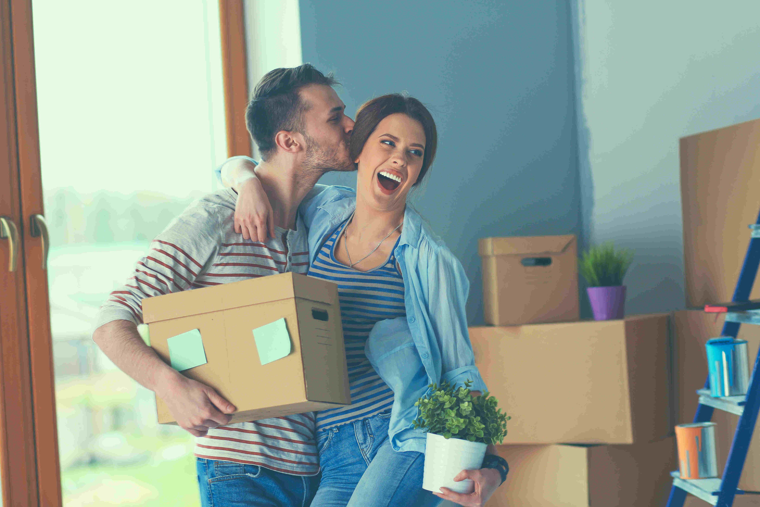 man kisses woman as they move into new home