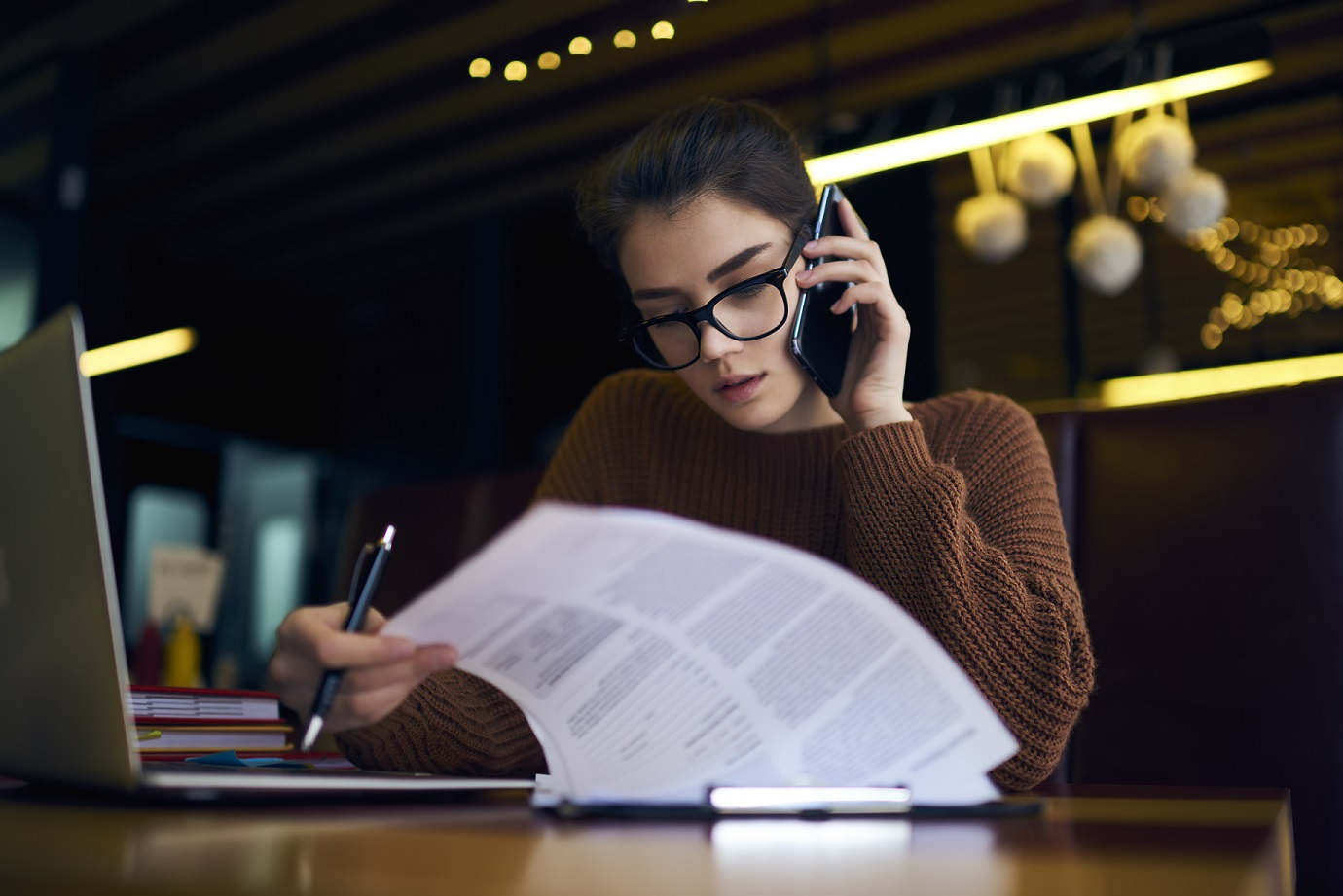 femal worker paging through documents while on phone