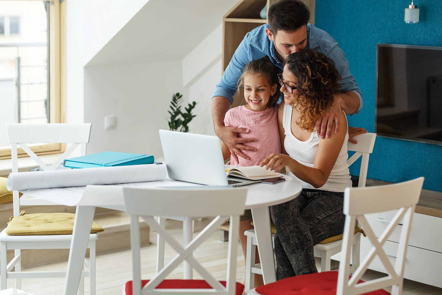 father kissies mother on forehead while child smiling at laptop