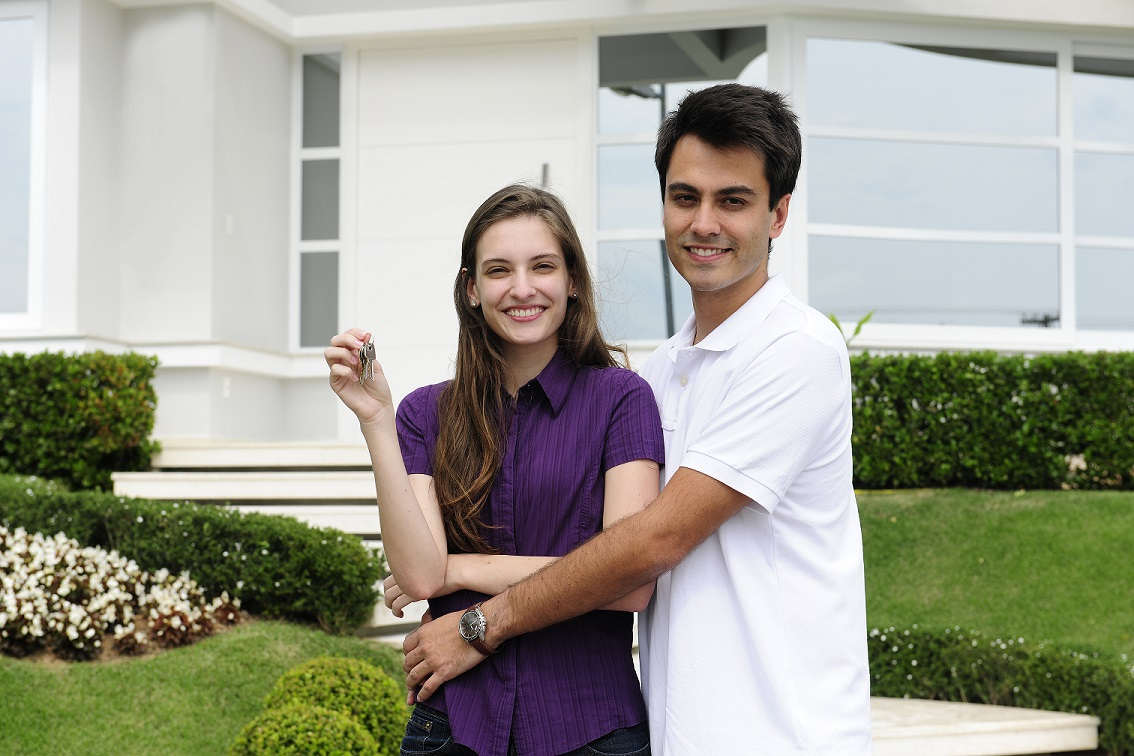 young man with arms around woman holding house keys with home in background