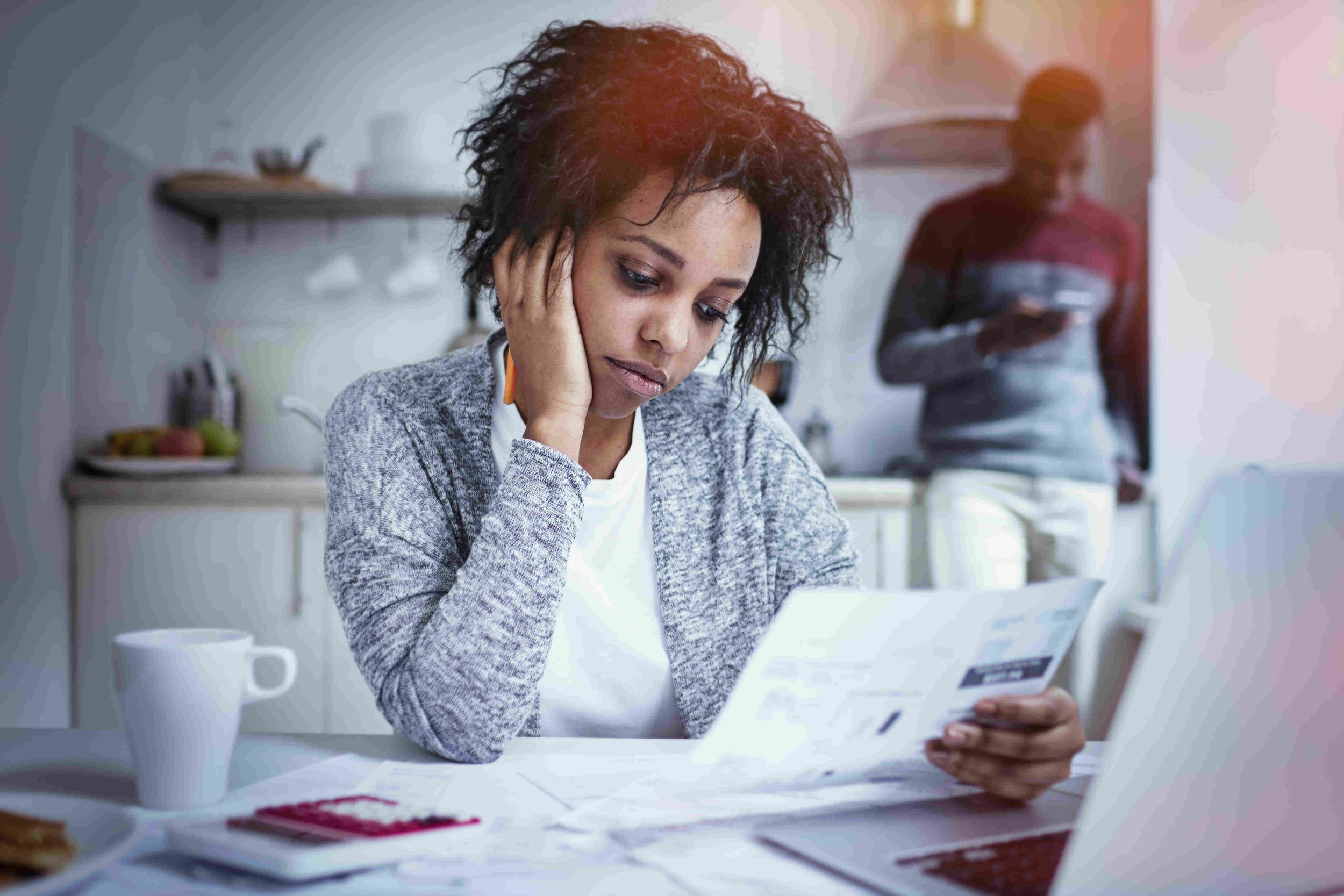 young mother in kitchen staring at documents with son in the background on a cellphone