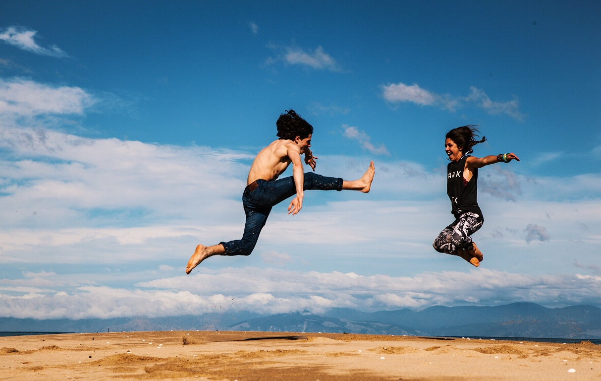 man and woman leap to each other at a beach