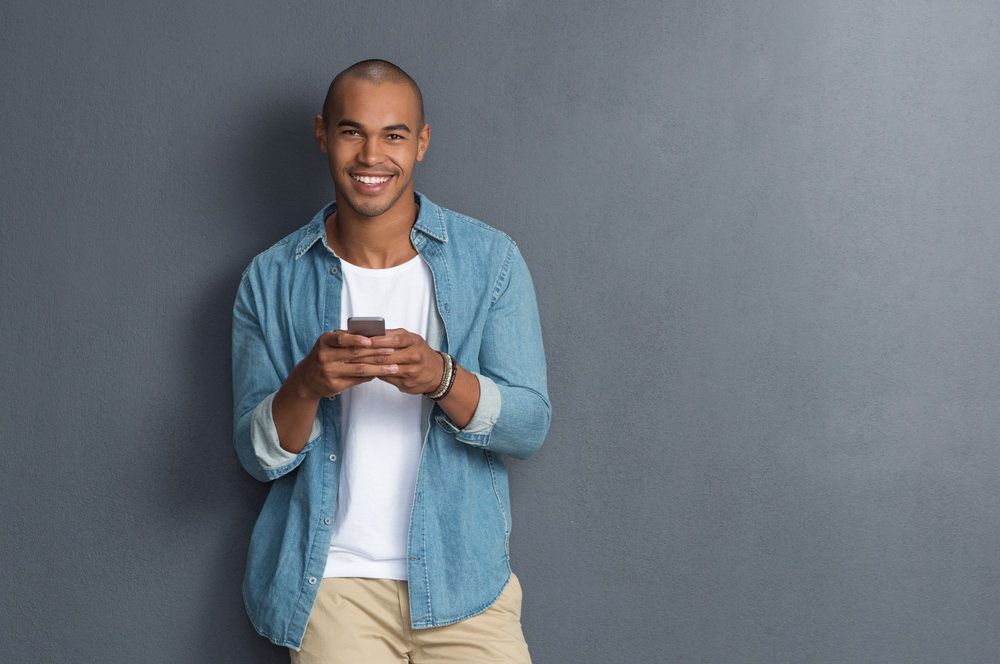young african american man smiling holding phone.jpg