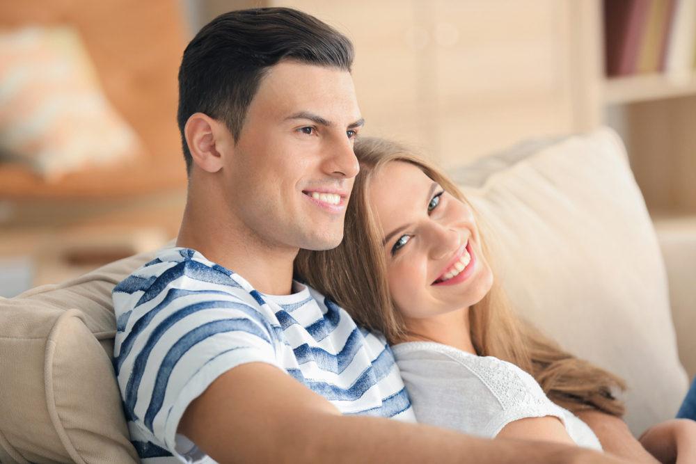 young couple smiling on sofa.jpg