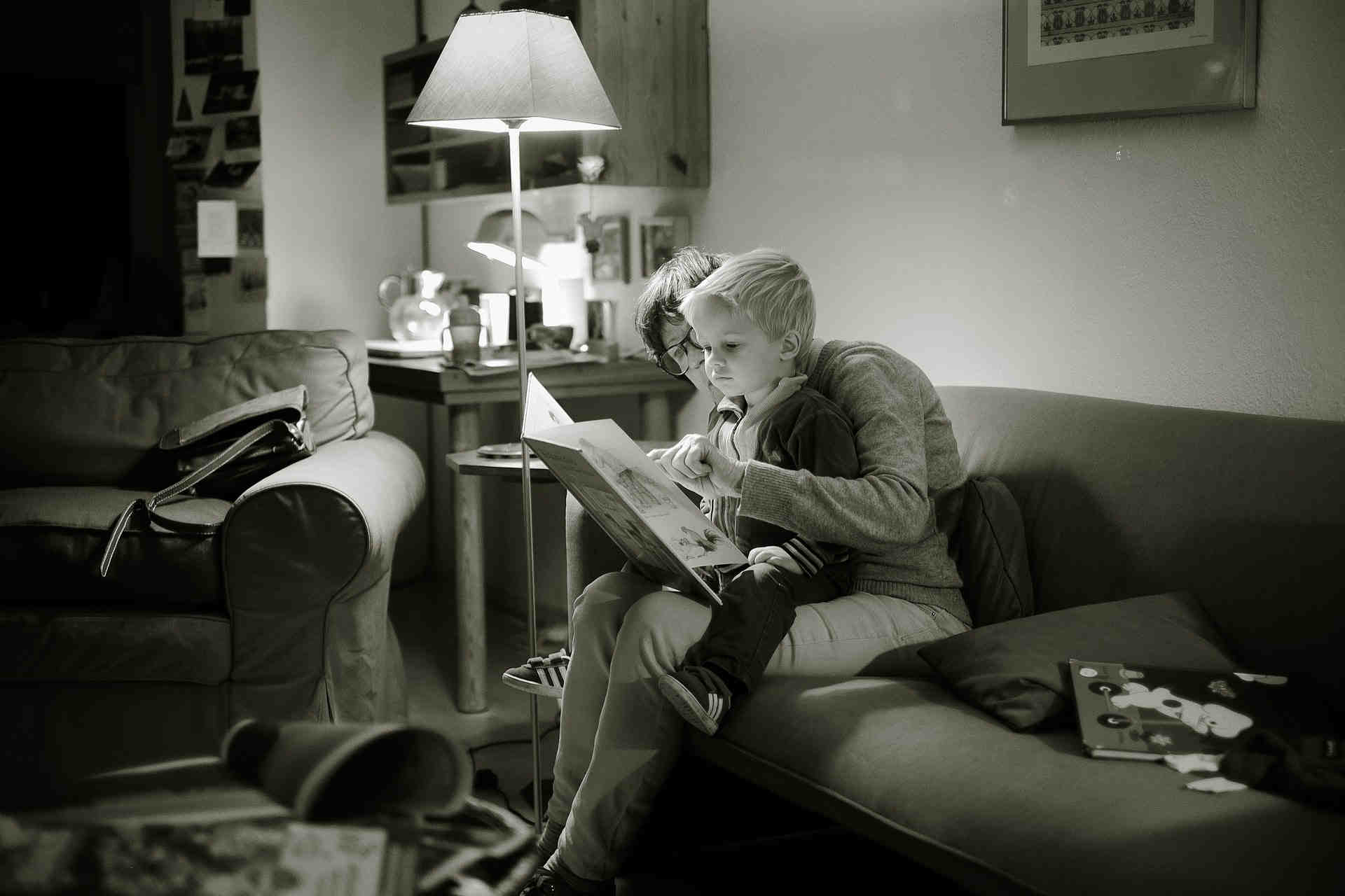 woman reading to boy in living room black and white (1).jpeg