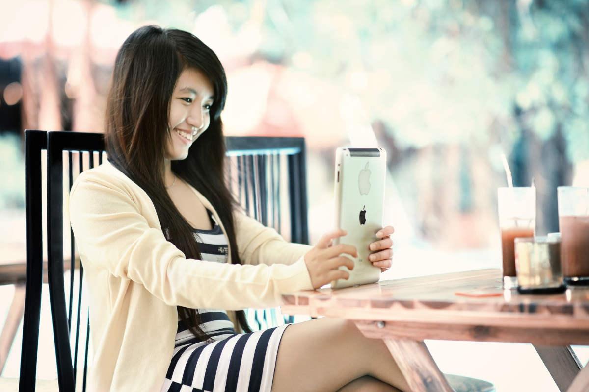 asian woman smiling at ipad.jpg
