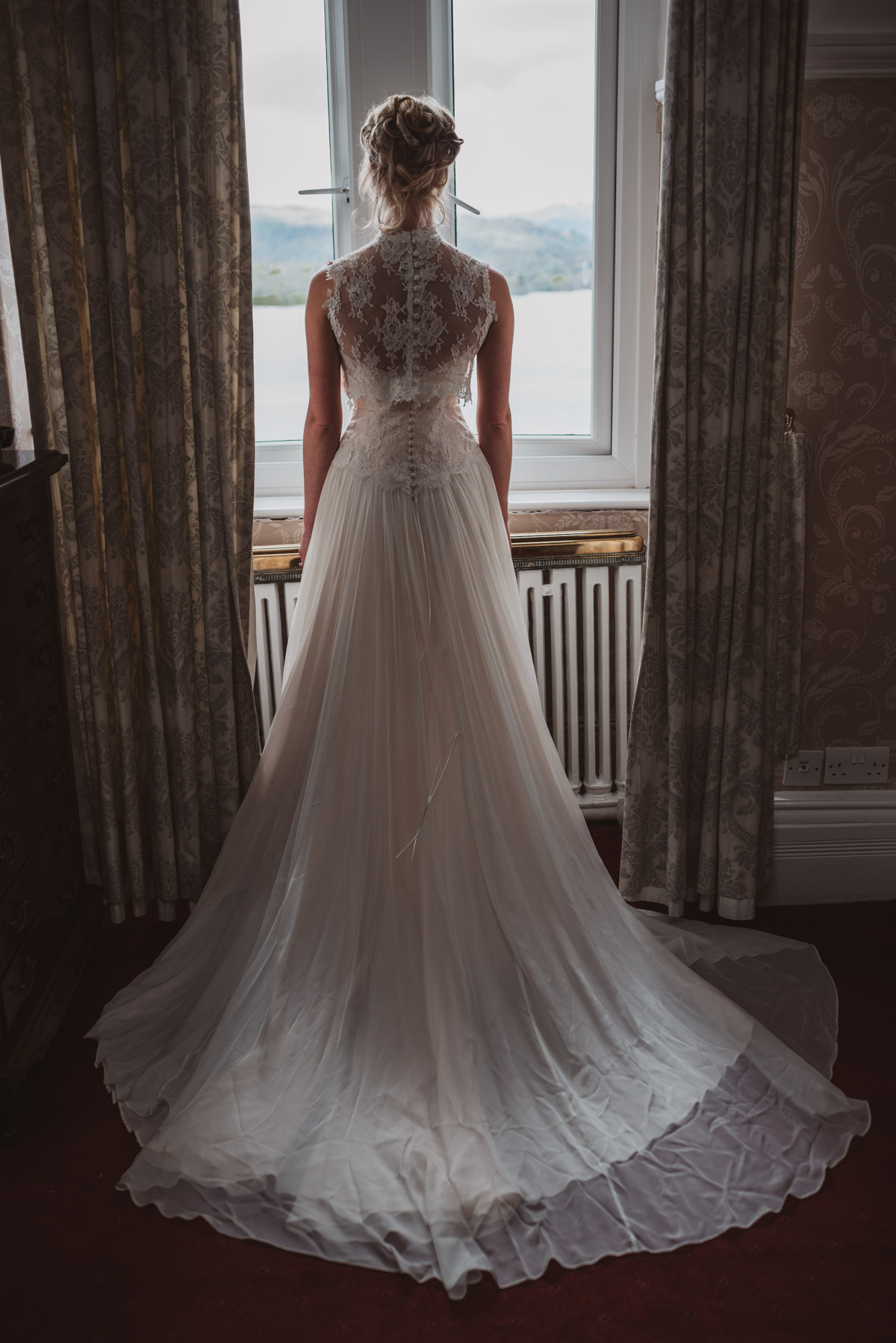 bride in front of window with lake backdrop