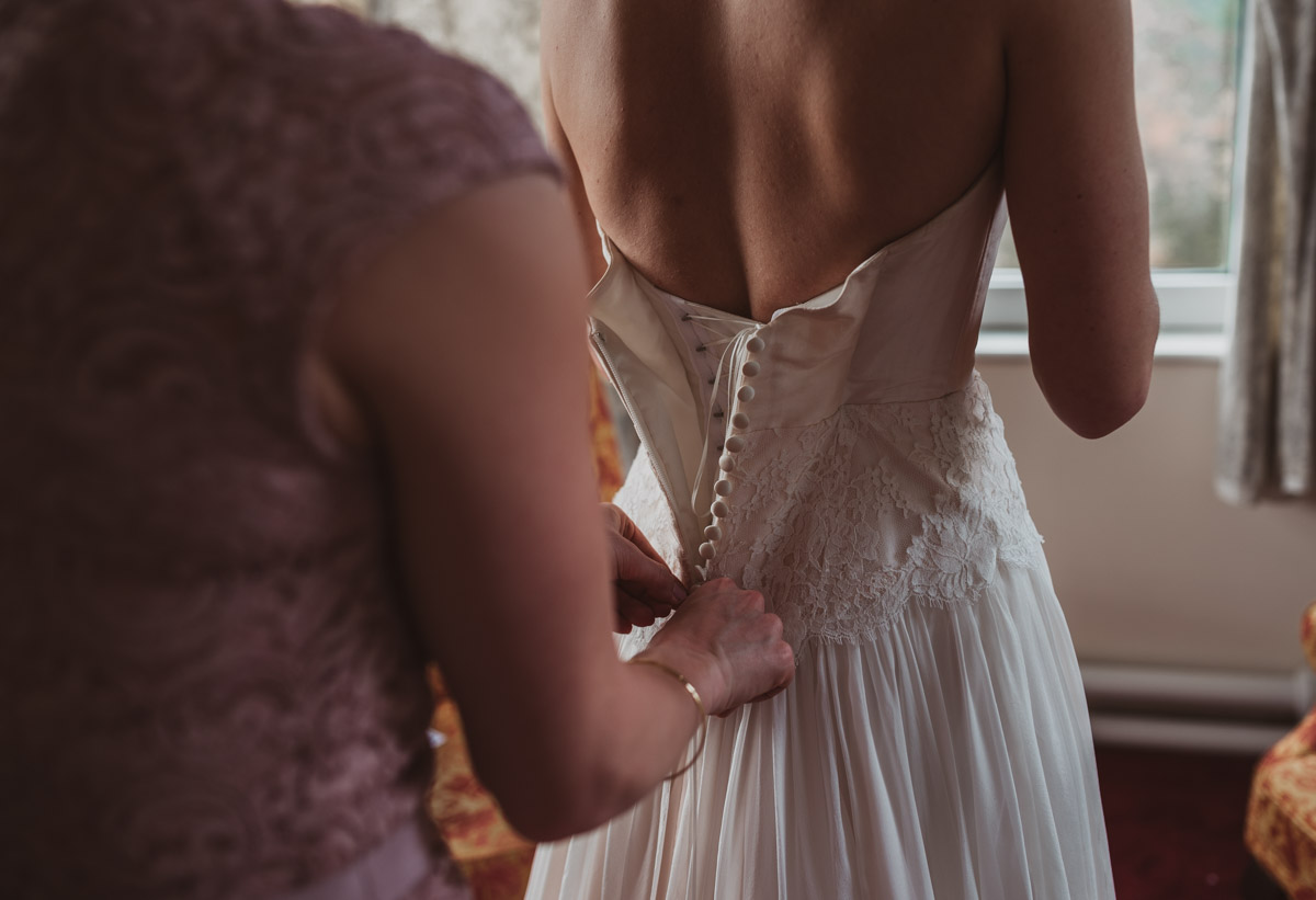 Lake District wedding - putting dress on