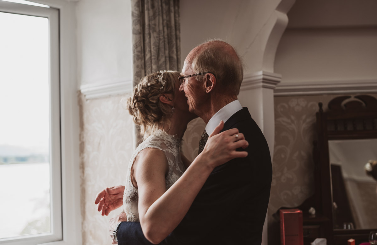 father of the bride and bride hugging natural